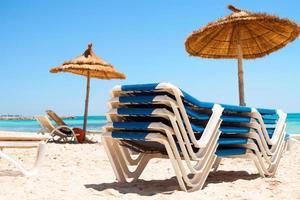 solstolar och parasoll på stranden foto