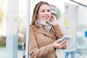 kvinna som väntar vid busshållplatsen