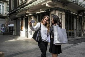 två tjejer gör selfie på gatan