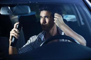 man gör hårvård i bilen