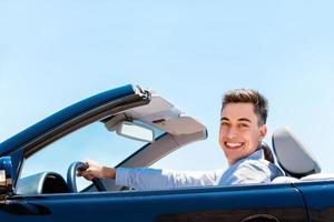 attraktiv ung man som kör cabriolet.