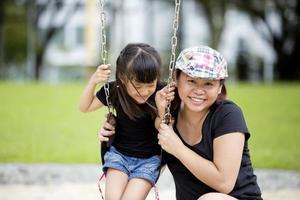 ung asiatisk mor och dotter som leker i park