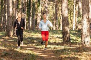 två vackra unga kvinnor som springer genom parken