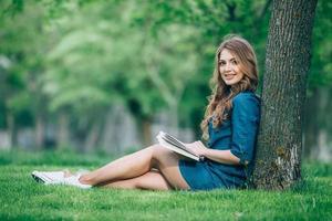 flicka som läser en bok i park