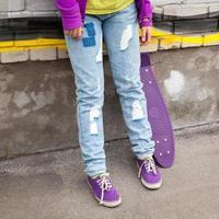 tonåring i jeans och gummiskor med skateboard