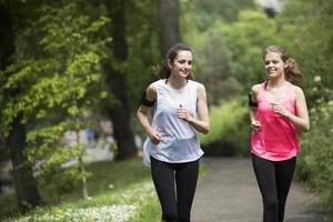 två sportiga kvinnor som springer utomhus i en naturlig miljö. foto