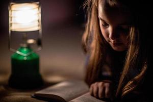 flicka läser bok i belysning lampa