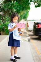 liten asiatisk tjej i thailändsk skoluniform