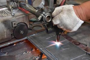 arbetare skär metallplåt foto