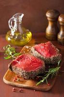 rå nötköttbiff med kryddor och rosmarin på träbakgrund foto