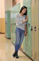 sorglig gymnasiet flicka i korridoren av skåp foto