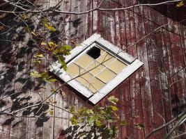 diamantformat fönster på gammal röd ladugård