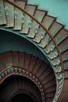 forntida interiör med gamla träspiraltrappor foto
