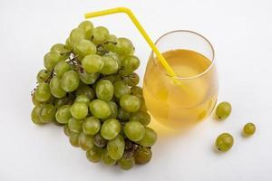 vit druvsaft och druvor på vit bakgrund foto