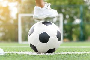 fötter av en pojke som bär vita sneakers som kliver på en fotboll foto