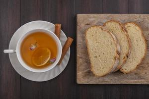 matfotografering platt låg av en kopp te med bröd på träbakgrund foto