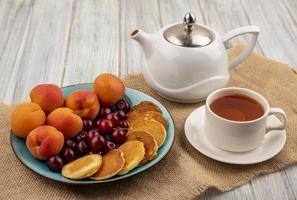 te med pannkakor och frukt på neutral bakgrund foto