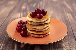 pannkakor med körsbär på träbakgrund