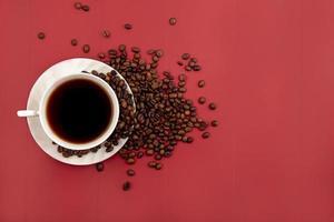 mat fotografering platt låg av en kopp kaffe och kaffebönor på röd bakgrund med kopia utrymme