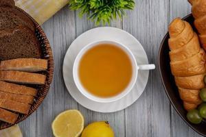 matfotografering platt låg av en kopp te centrerad mellan bröd och bär foto