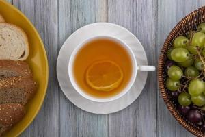 matfotografering platt låg av en kopp te centrerad mellan bröd och bär