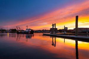 kustbevakningsbåt som drar in i hamnen vid solnedgången foto