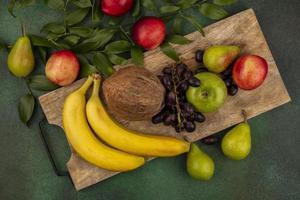 blandad frukt på skärbräda på grön bakgrund