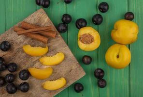 blandad frukt på skärbräda på grön bakgrund foto