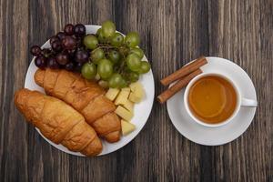 frukt och bröd med te på träbakgrund foto