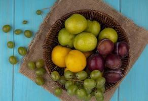blandad frukt i en korg på blå bakgrund