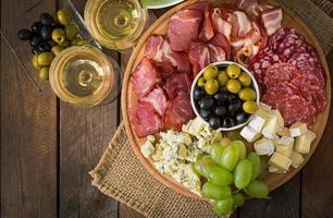 antipasto cateringfat med bacon, ryckig, salami, ost och druvor foto