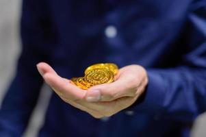 affärsman som håller guldmynt