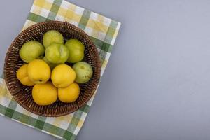 ovanifrån av frukt i en korg på rutigt tyg