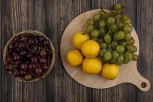 blandad frukt på skärbräda på träbakgrund foto