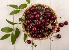 ovanifrån av körsbär i en korg på träbakgrund foto