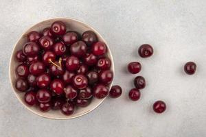 körsbär i en skål på vit bakgrund foto