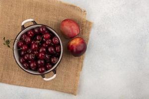 diverse röd frukt på säckväv neutral bakgrund foto