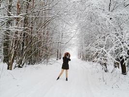 lettland, 2020 - kvinna i en svart parka som tar ett foto i ett snöigt landskap