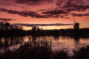 silhuett av byggnader nära vattendrag vid solnedgången
