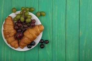 croissanter och druvor på grön bakgrund med kopieringsutrymme foto