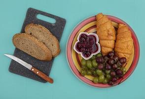 bröd och frukt på blå bakgrund foto