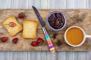 rostat bröd med sylt och te på träbakgrund