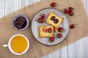 rostat bröd och frukt på en tallrik på grå träbakgrund foto