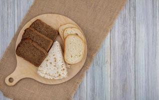 skivat bröd på säckväv på träbakgrund
