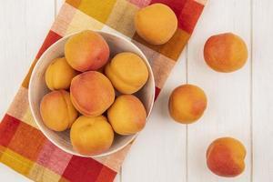 aprikoser på rutigt tyg på träbakgrund foto