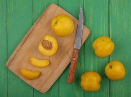 aprikoser med kniv på skärbräda på grön bakgrund foto