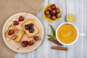 rostat bröd med frukt och te på en grå träbakgrund foto