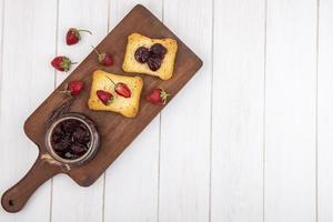 bär och rostat bröd på en vit träbakgrund med kopieringsutrymme foto