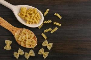 rå pasta på en träbakgrund med kopieringsutrymme foto