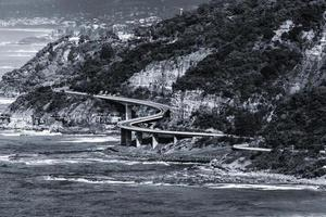 gråskala av en bro nära havet